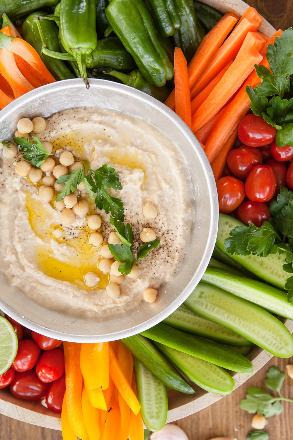 large bowl of homemade hummus surrounded by colorful local vegetables