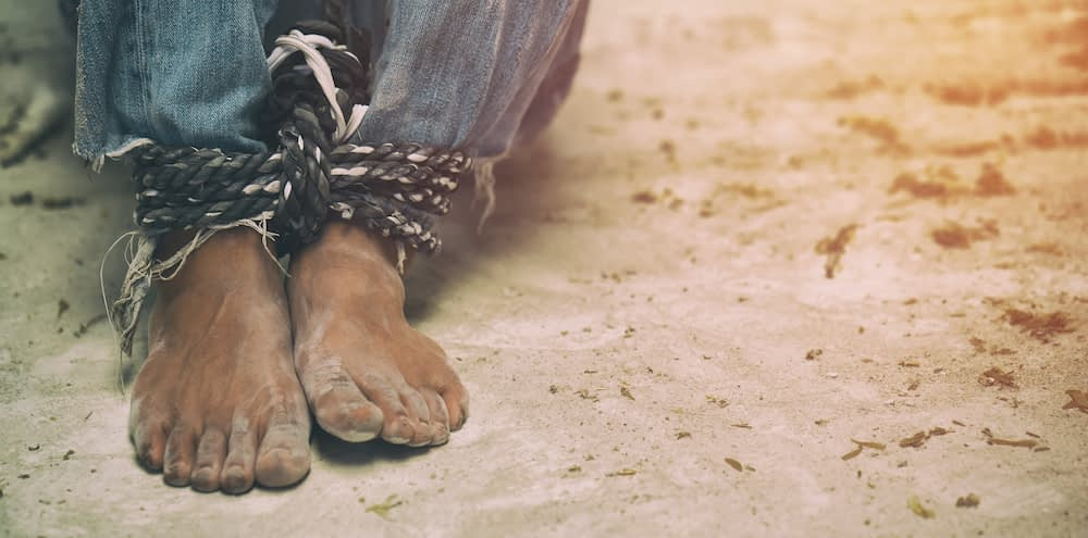 A man's feet bound together by a rope on a dusty floor