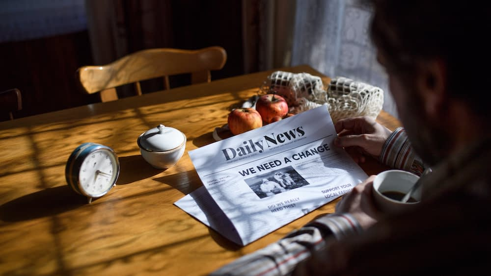 """A man reads a newspaper at his kitchen table. The headlines reads """"We Need A Change."""""""