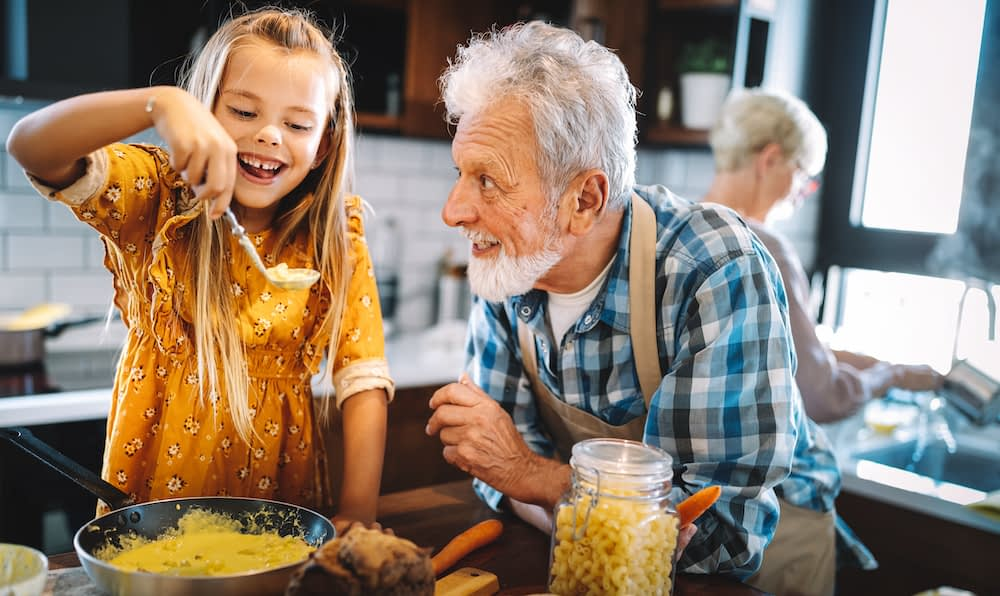 Child preparing macaroni and cheese meal for family, with grandfather watching excitedly.