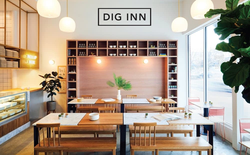 """Inside view of """"Dig Inn"""" healthy fast casual restaurant with modern aesthetic, well-organized space."""