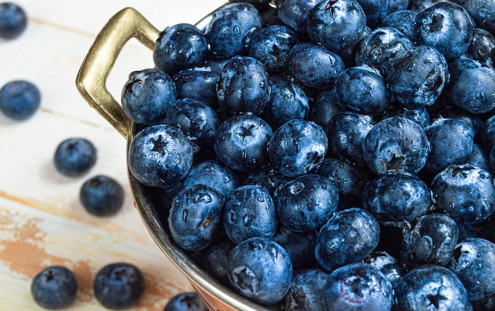 Fresh blueberries heaped in a copper bowl