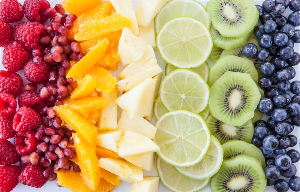 Fresh fruits lined up in rainbow-colored rows.