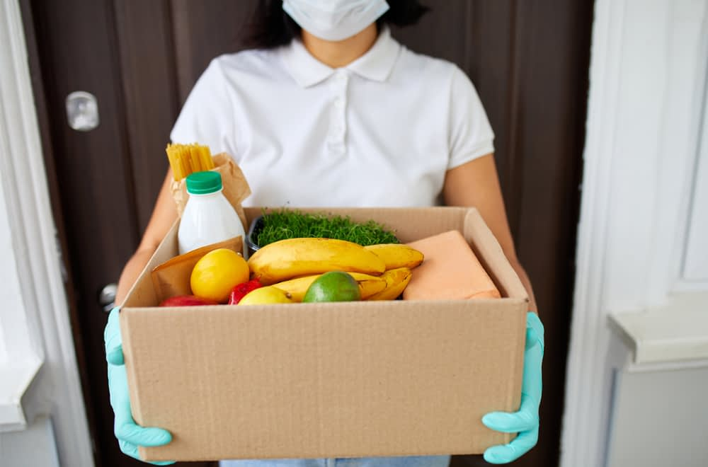 A woman in a mask and gloves holds a cardboard box of milk, pasta, and fresh produce,