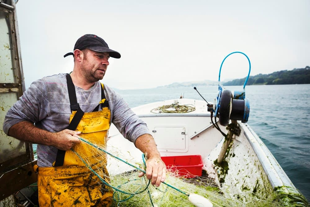 a fisherman on a boat hauling in the fishing net