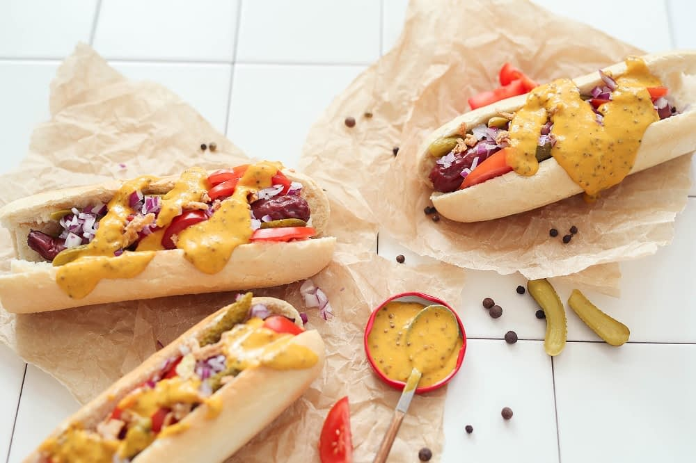 three hot dogs with onions, tomatoes, pickles, and honey mustard sit on crumpled paper. a bowl on honey mustard, a unique topping for honey mustard, sits beside them.