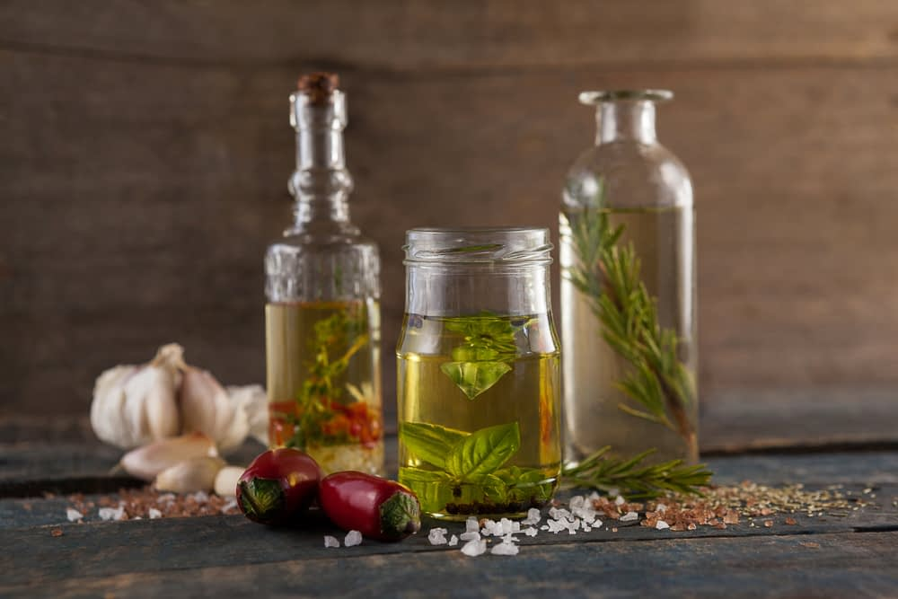 oil infused with leftover herbs in a glass container