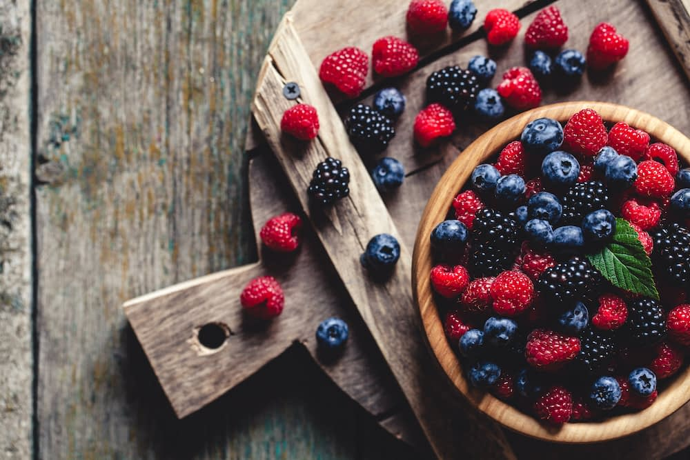 A bowl of vibrant berries like raspberries, blueberries, and blackberries on a wooden cutting board