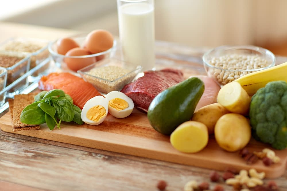 Image of hard-boiled egg, spinach, broccoli, potatoes, salmon, banana, and other vitamin B-rich foods on dinner table spread.