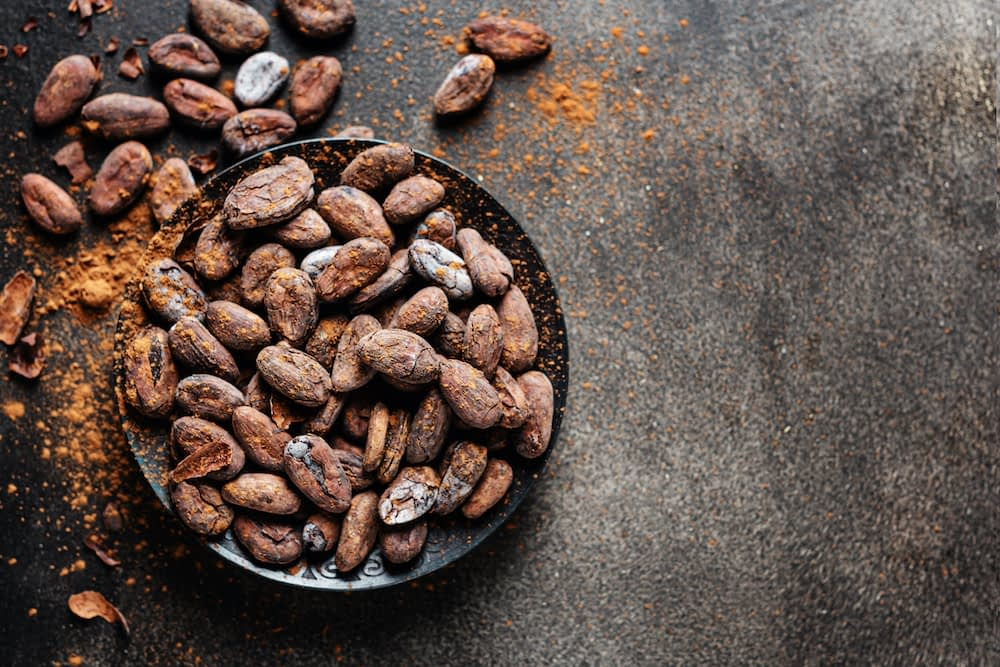 Bowl of cacao beans and cacao powder on black background.