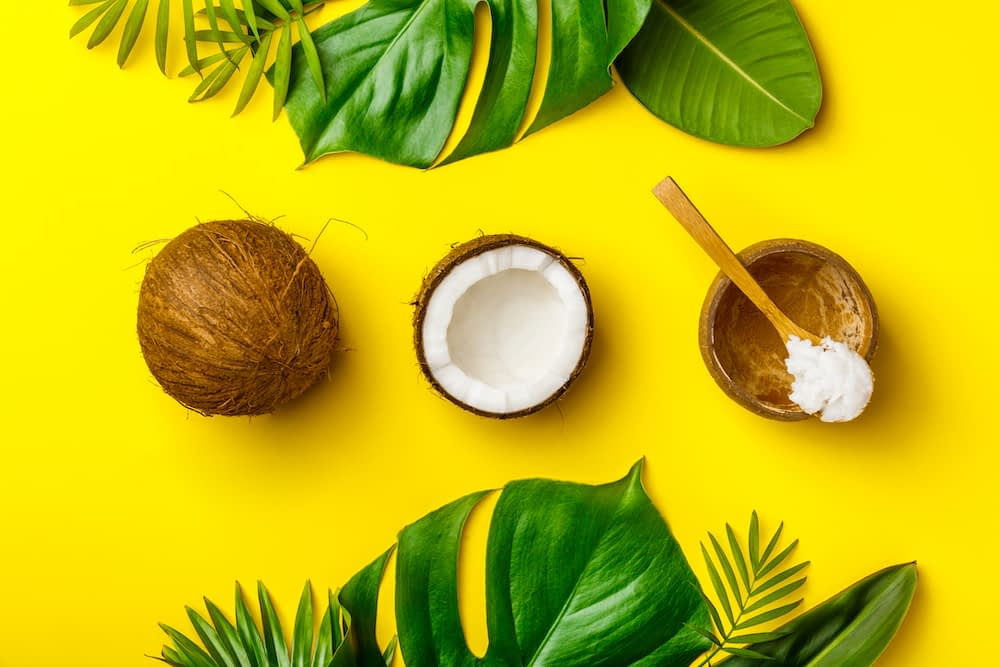 Coconut split open with spoon collecting coconut flesh, surrounded by leaves on yellow background.