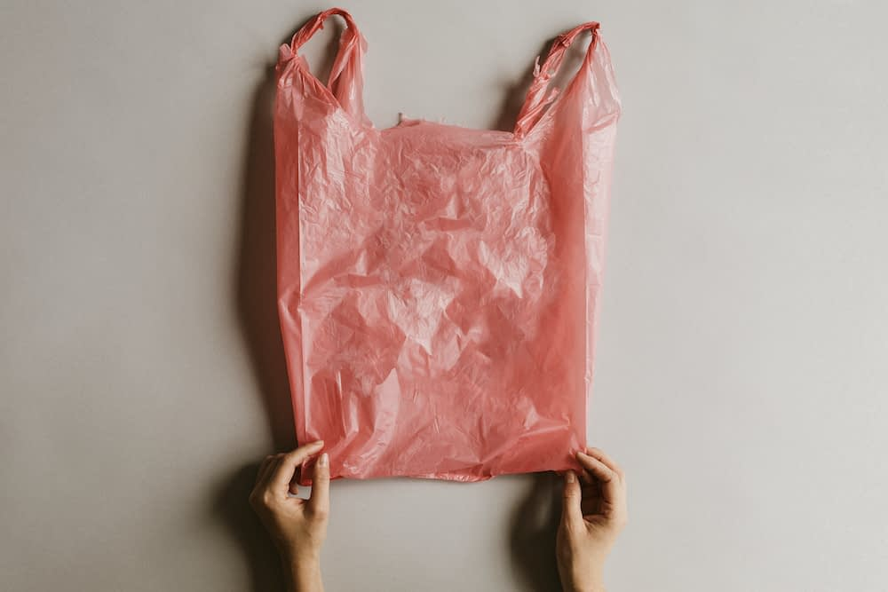 a pink single use grocery bag that has been used. Plastic bag being held by two hands.