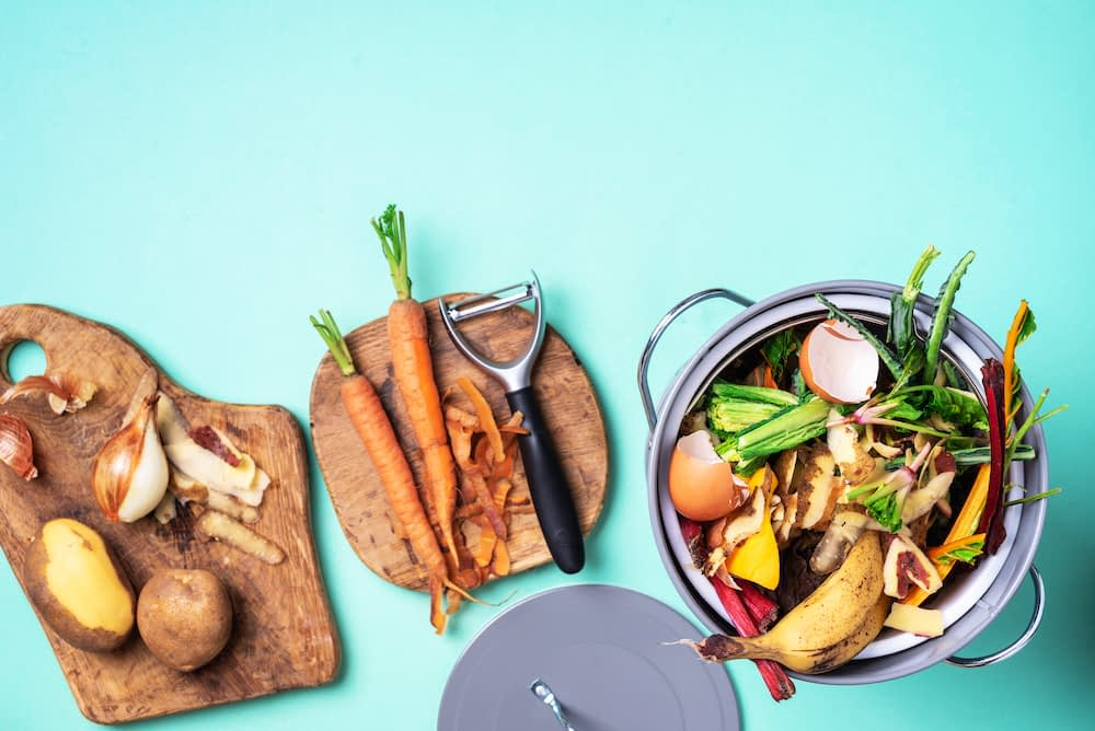 an assortment of vegetable scraps on wooden cutting boards and metal compost bin