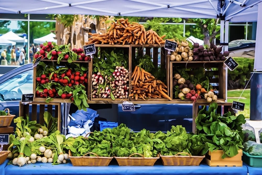 a farmers market stand with fresh locally grown carrots, greens, beets, and onions