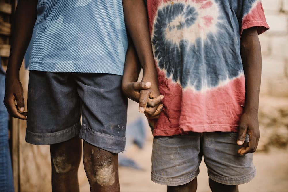 Two young boys in dirty clothes hold hands