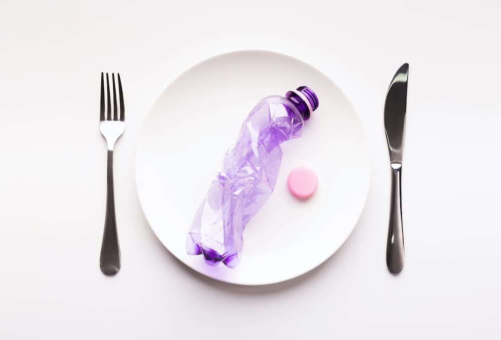 crumpled single-use plastic bottle on a plate with a fork and knive