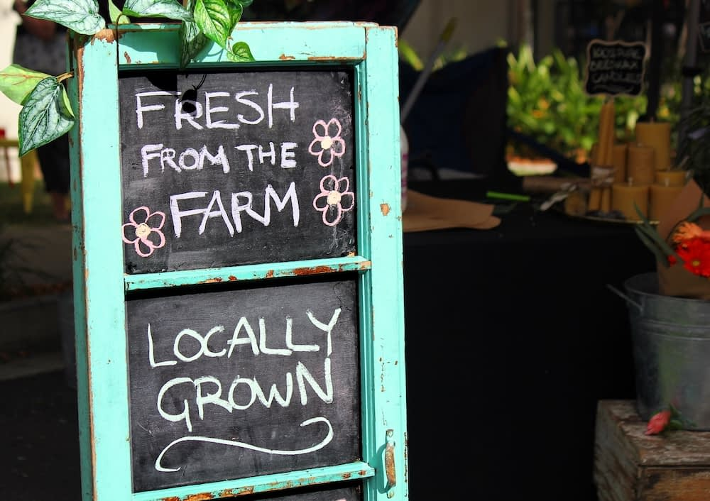 sign at a local farmers market that reads fresh from the farm, locally grown