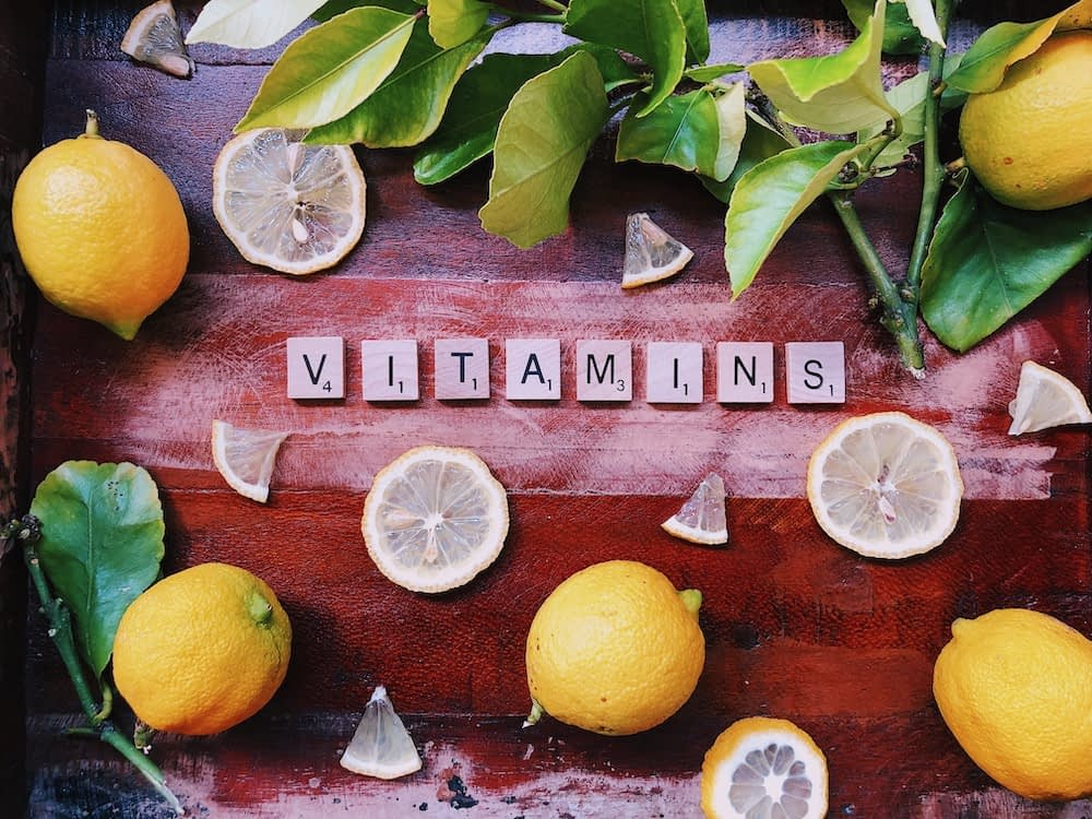 the word vitamins spelled out in scrabble letters surrounded by leaves and lemons