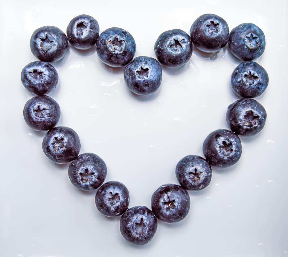 Fresh blueberries arranged in the shape of a heart
