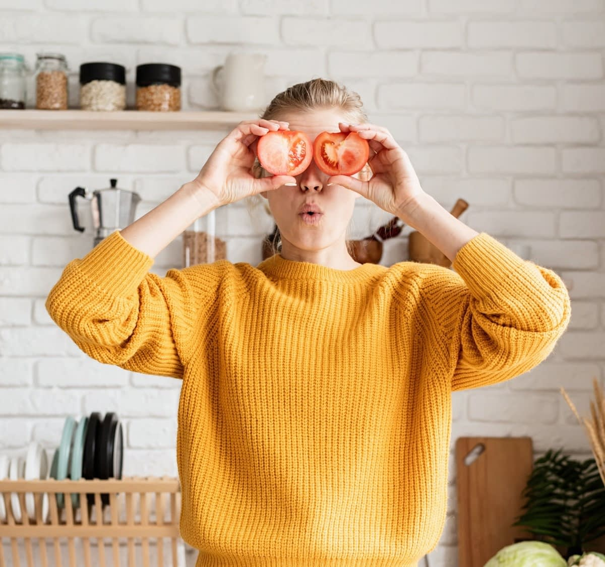 A woman in a yellow sweater stands in her kitchen, holding two tomato halves over her eyes