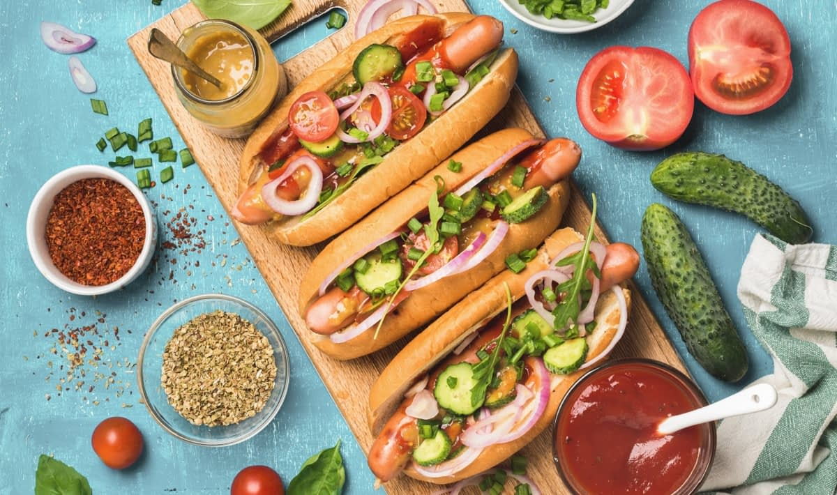 Three hot dogs with tomoato, onion and cucumber sit on a cutting board, with hot dog condiments around them