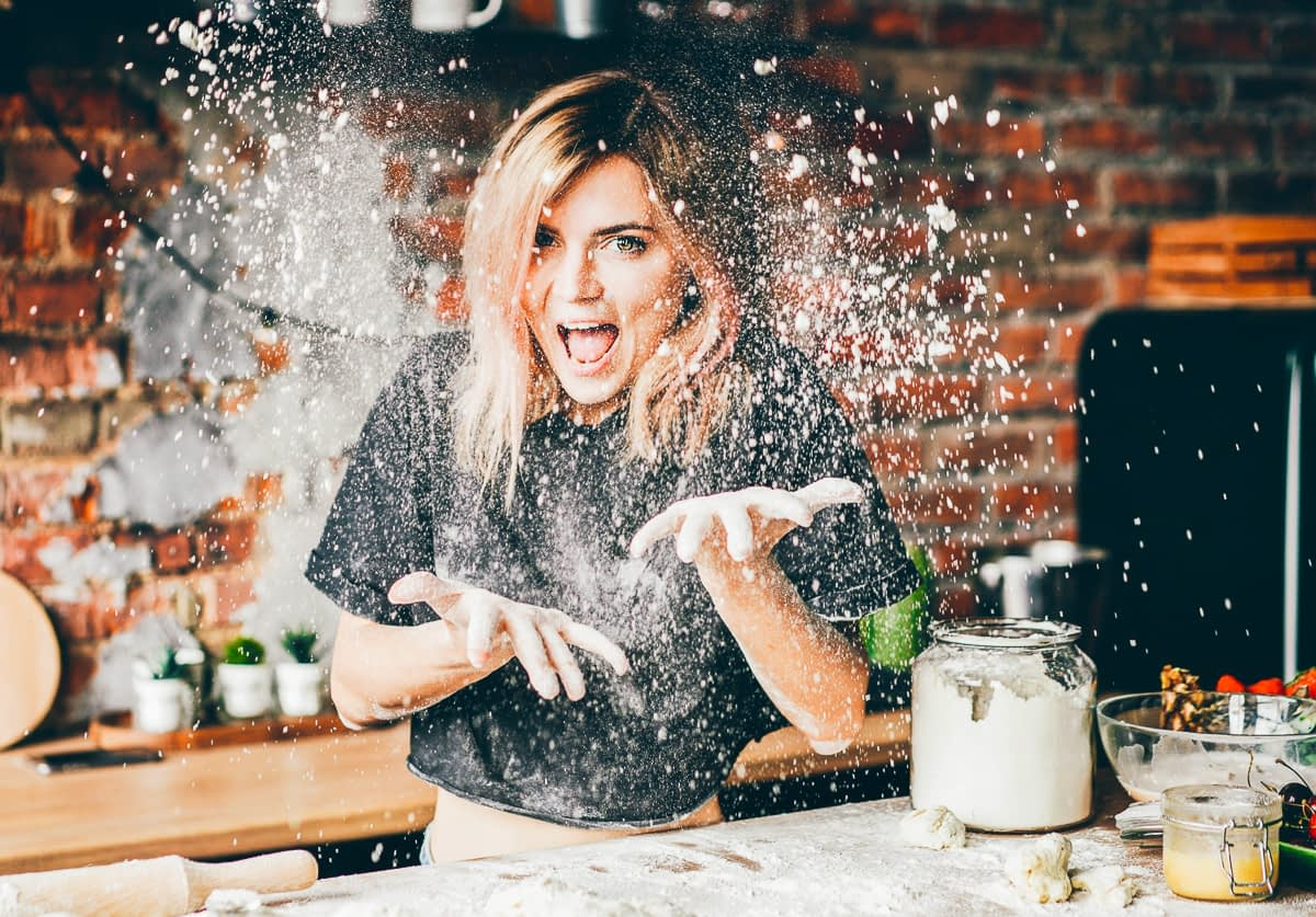 A woman smiles as she throws flour in her kitchen.