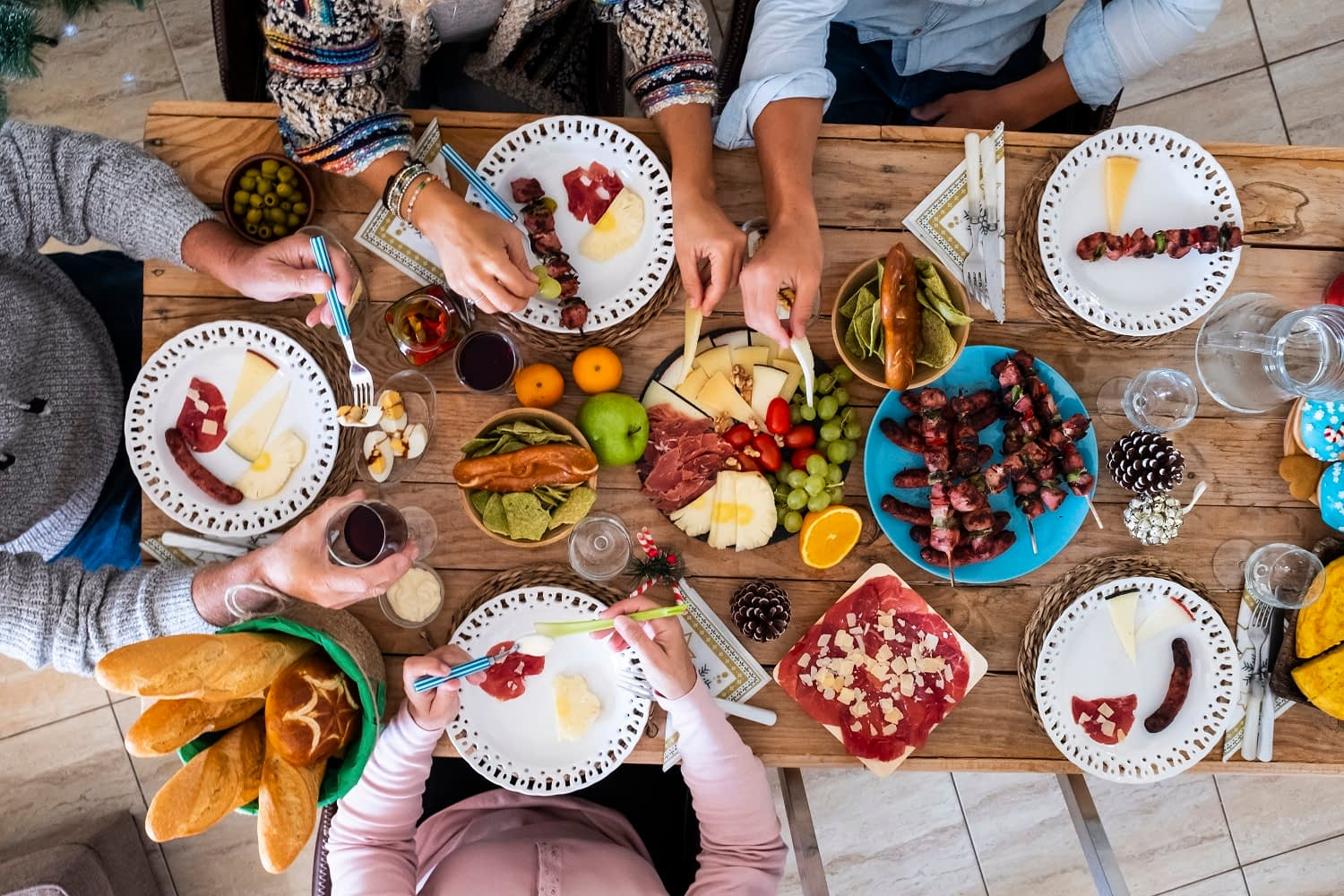 Family friends have fun together in winter eating food on a wooden table - vertical top view