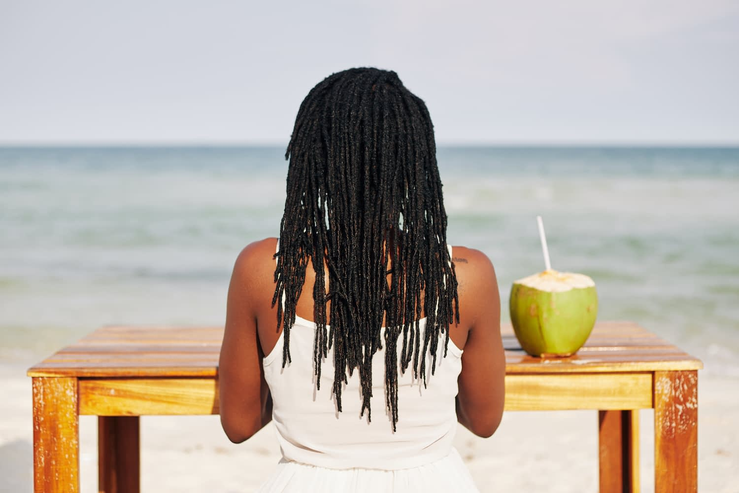 Young Black woman with dreadlocks sitting at table with coconut water, working on laptop ang enjoying sea view