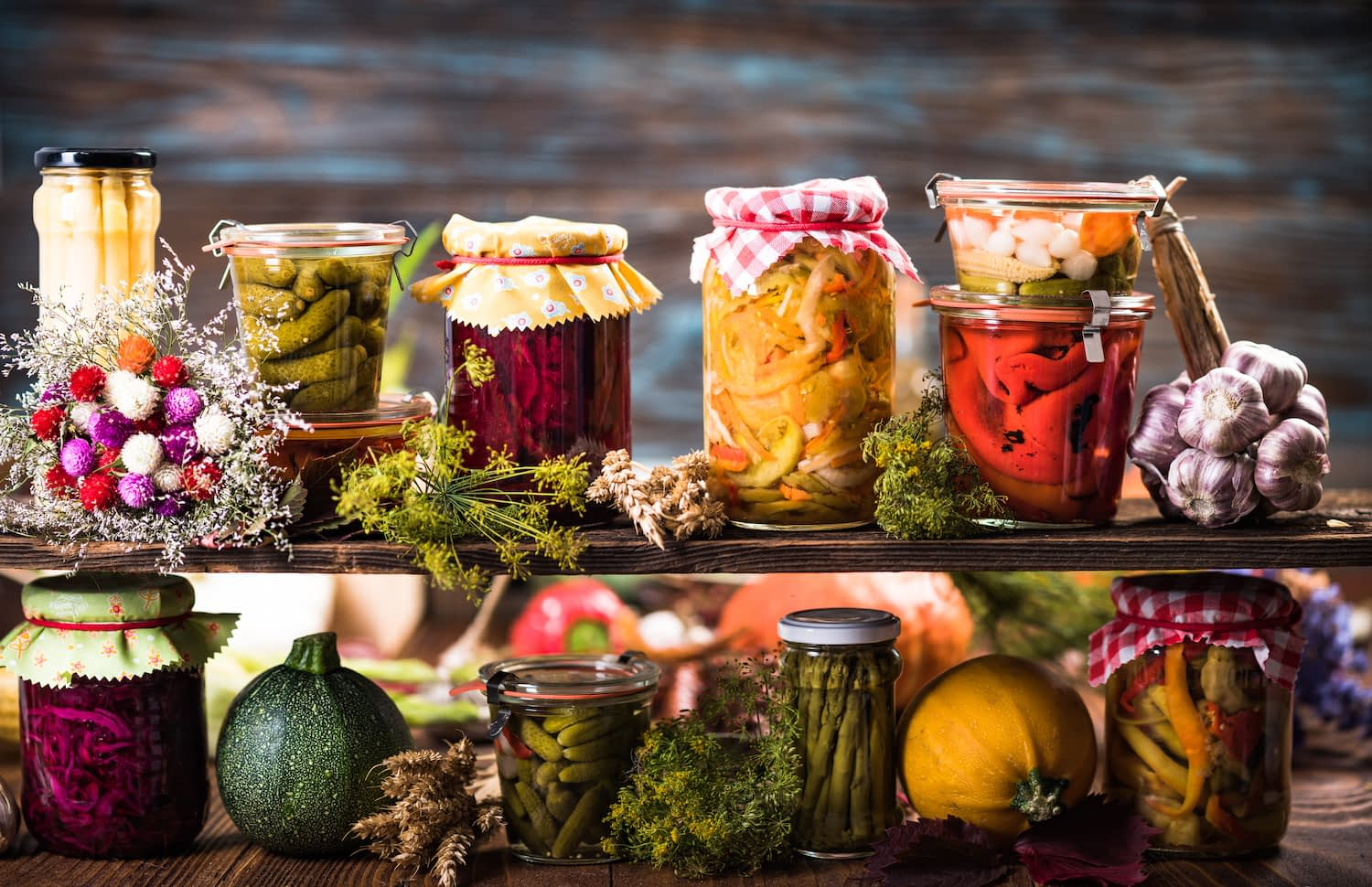 Jars of fermented foods on wooden table with pickles, kimchi, asparagus, peppers and other vegetables.
