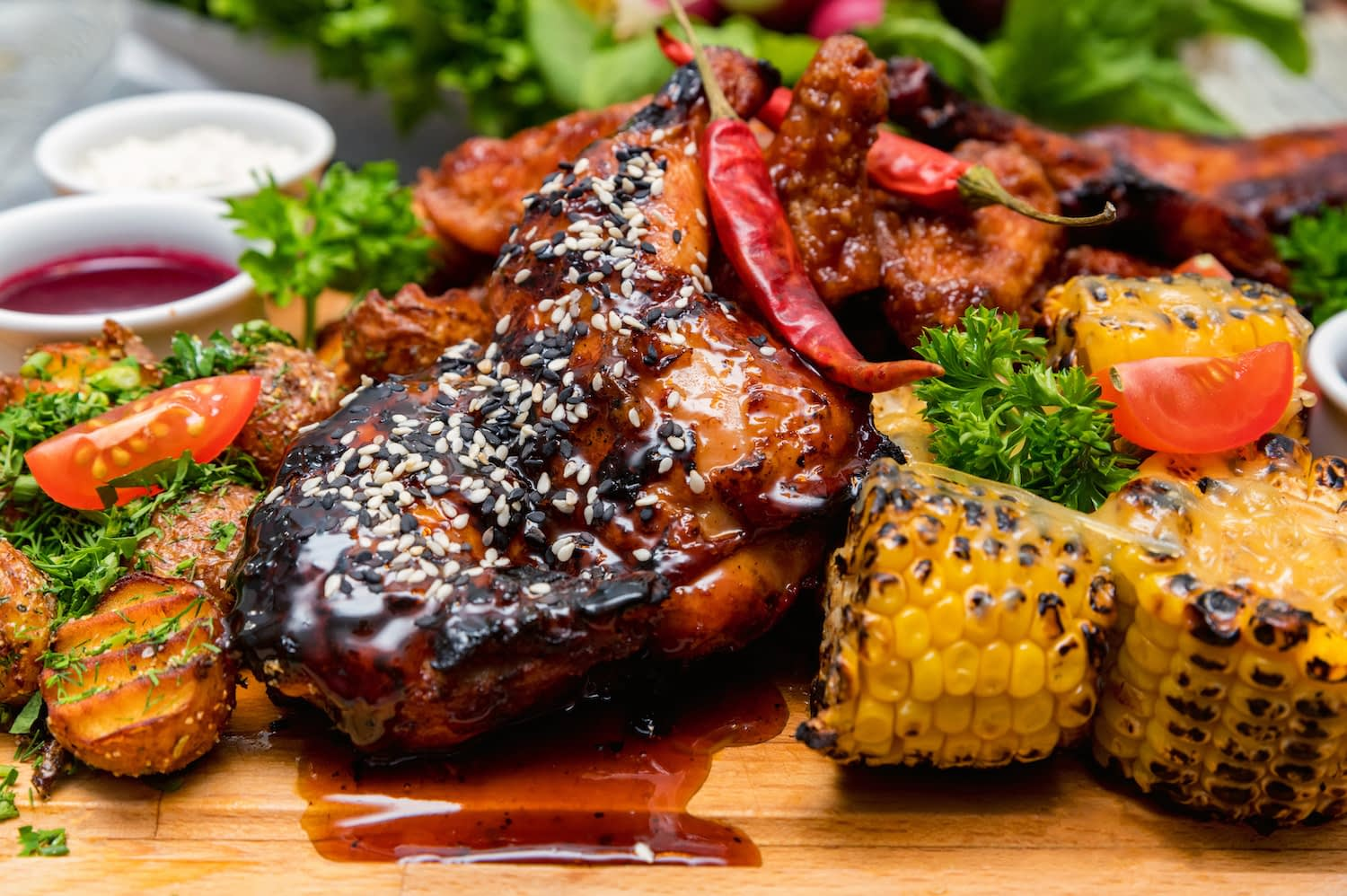 Barbecue chicken on a wooden table, surrounded by corn and potatoes.