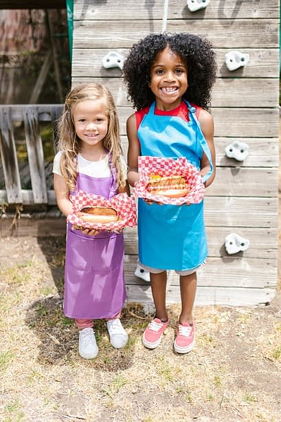 Two girls standing next to each other holding hot dogs and smiling