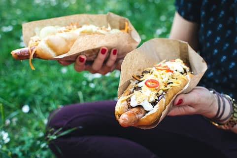 a person with red painted nails holds two heavily-topped hot dogs while sitting in a feild