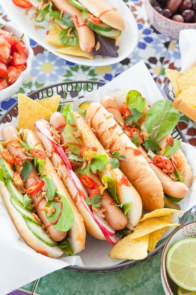 Three hot dogs with cucumber spinach, tomato, and onions, drizzled with ketchup,sit in a metal basjeket likes with paper, on top of a picnic table