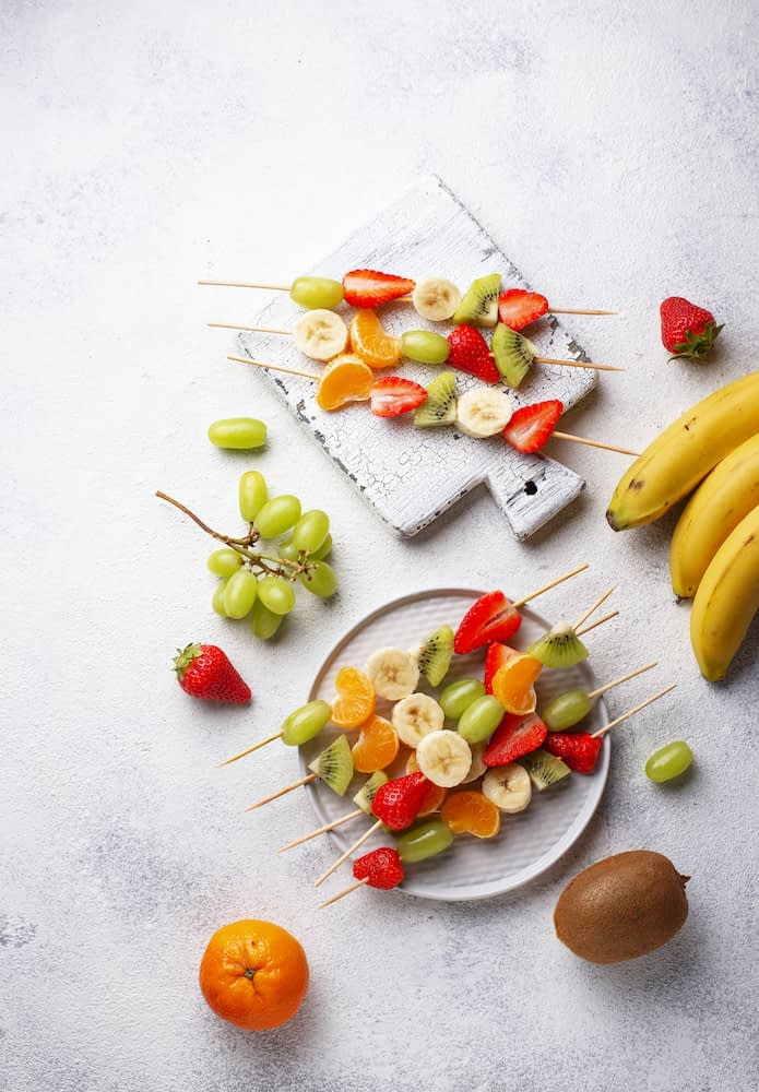 Brightly colored skewers of fruit on a white table.