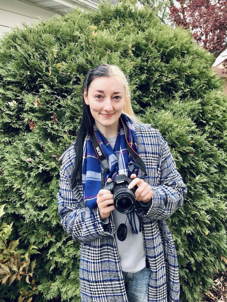 Photo of fermentation expert, Cambria Sinclair, holding camera and smiling in front of large bush.