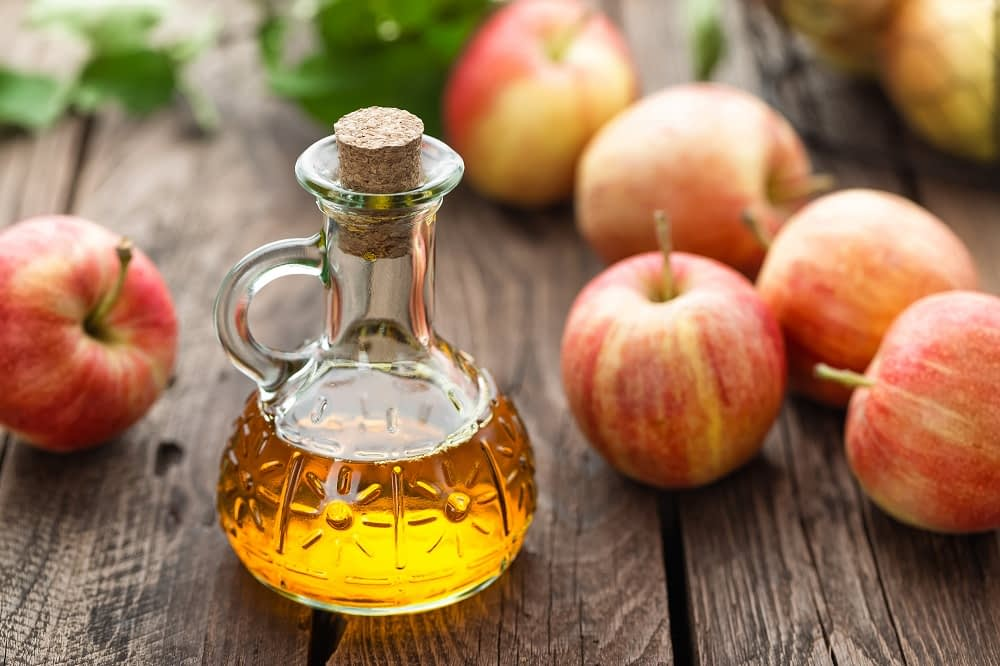 Small glass bottle of apple cider vinegar, a few apples lay in the background.