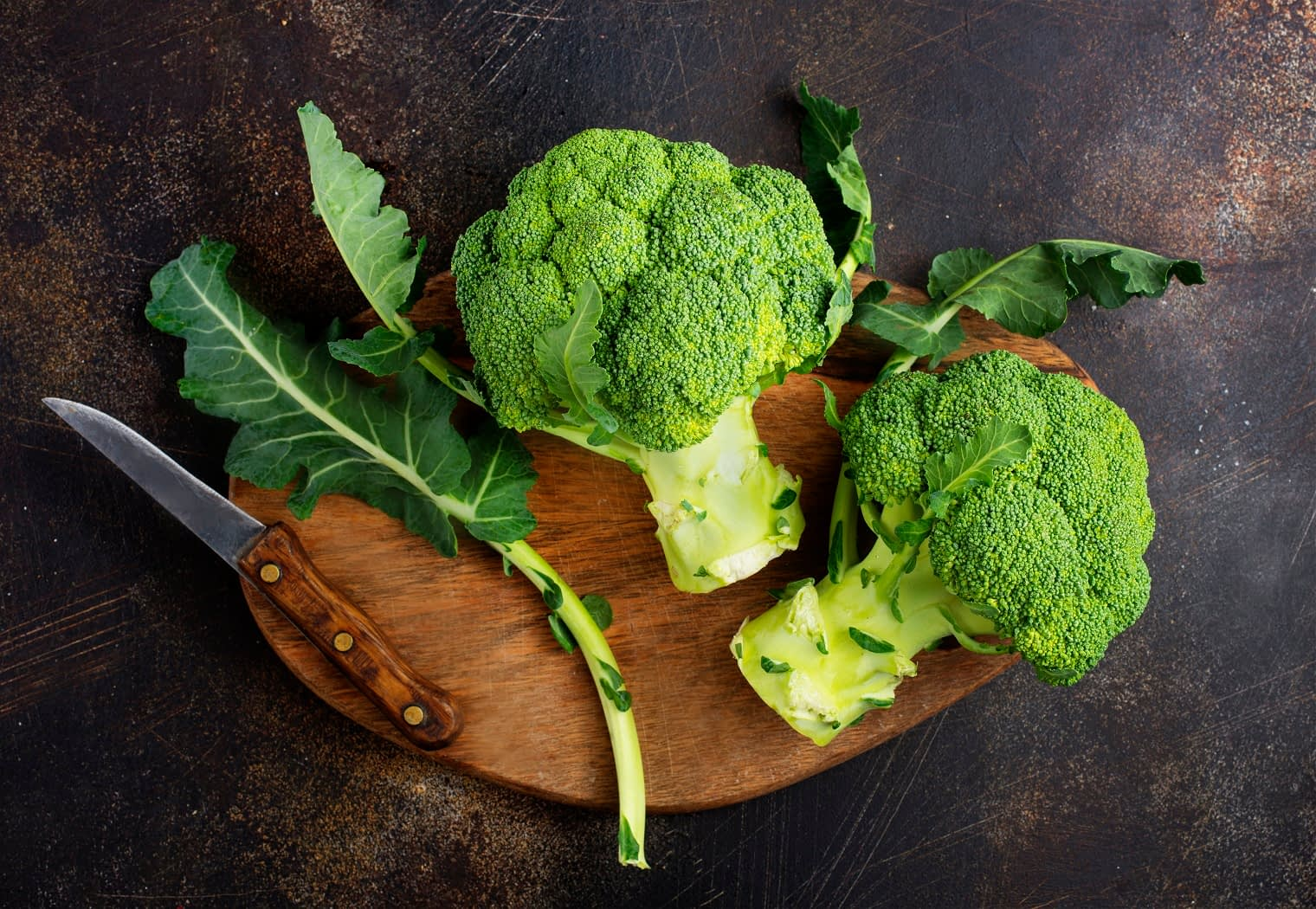 two heads of broccoli on a cutting board