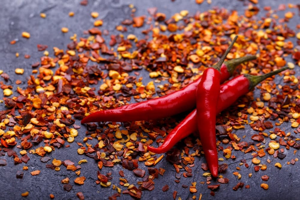 three chili peppers laying on top of chili pepper flakes