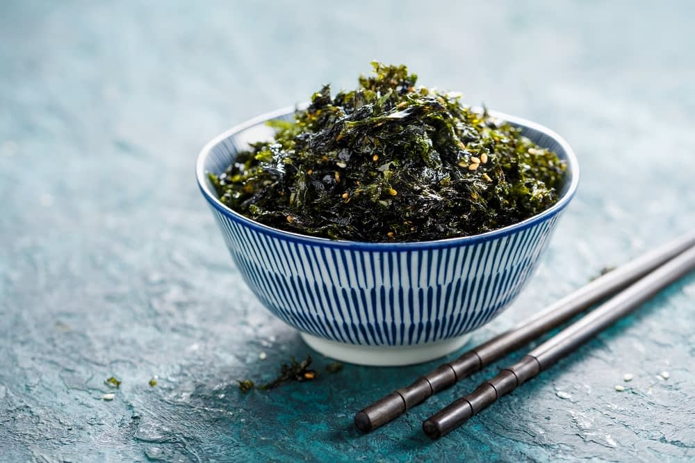 Crispy Nori Seaweed  in a bowl with sesame and sea salt and a pair of chopsticks