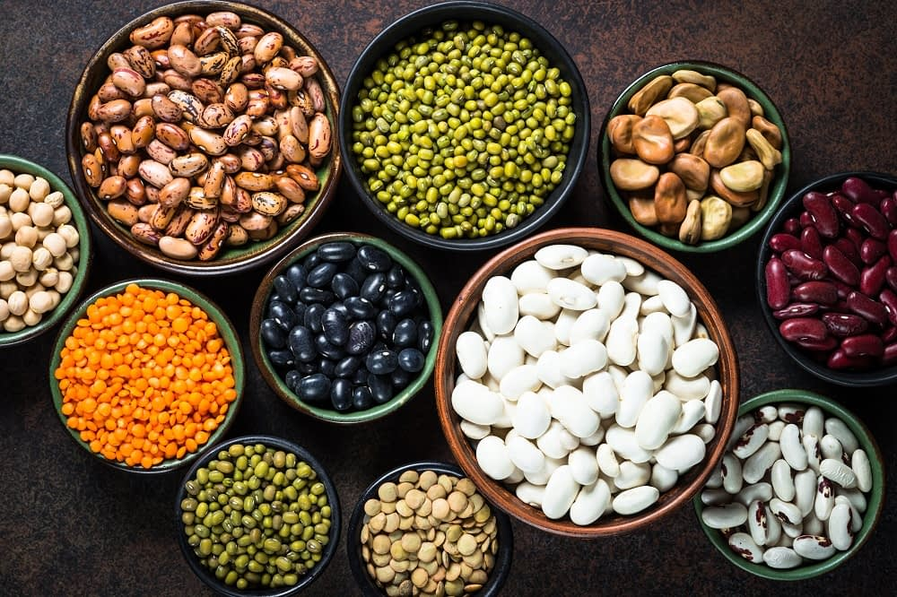 Legumes, lentils, chikpea and beans assortment in different bowls on stone table. Top view on dark background.