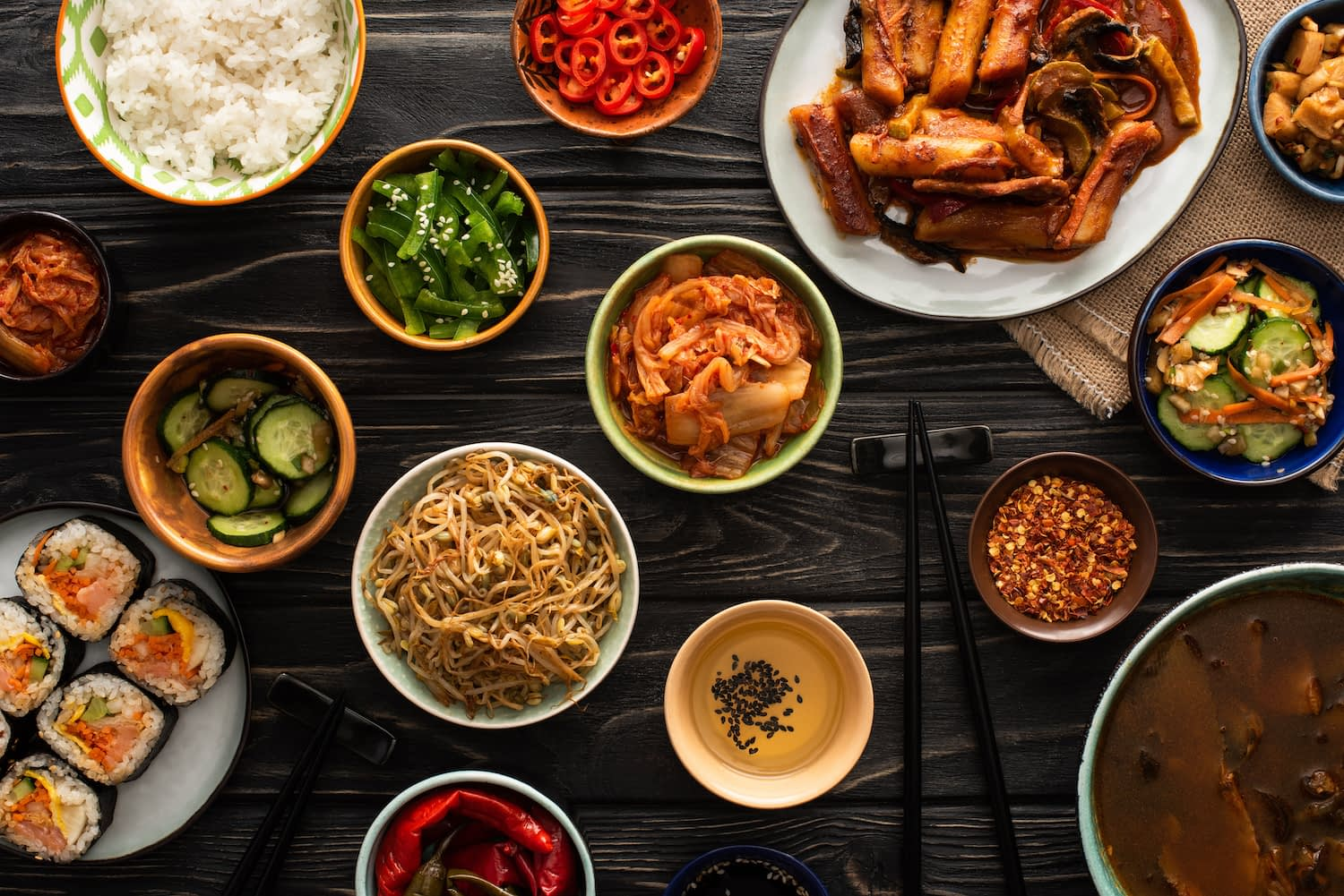 top view of korean traditional dishes near chopsticks and cotton napkin on wooden surface