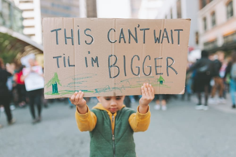 small boy holding a sign as a climate change activist