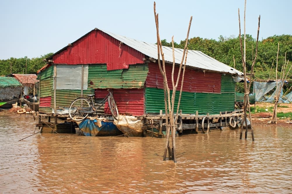 red house floating on muddy water in Cambodia