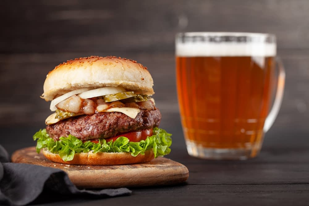 A burger on a wooden board next to a glass of beer.