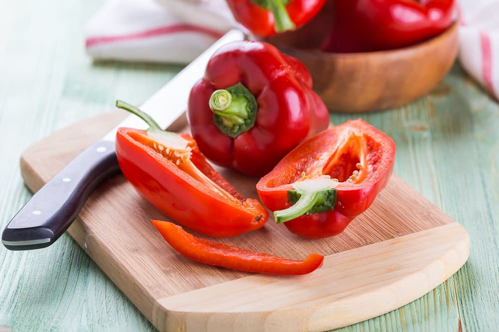 Fresh red bell peppers on a bright wooden background