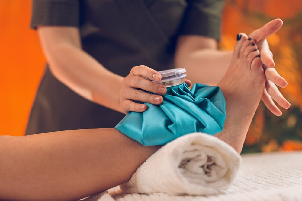 Nurse holding a blue ice pack on a swollen ankle.