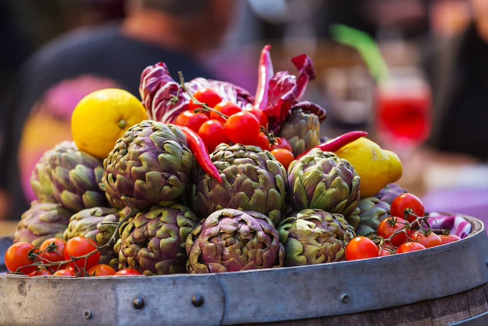Artichokes and tomatoes stacked together in a tin tub.