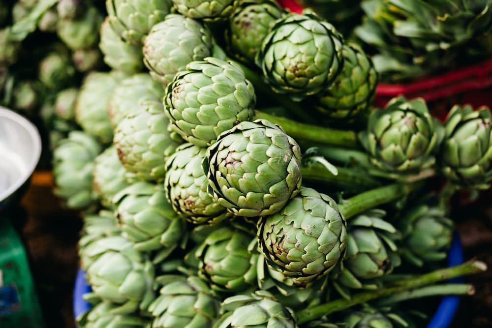 A pile of artichokes stacked on top of each other.