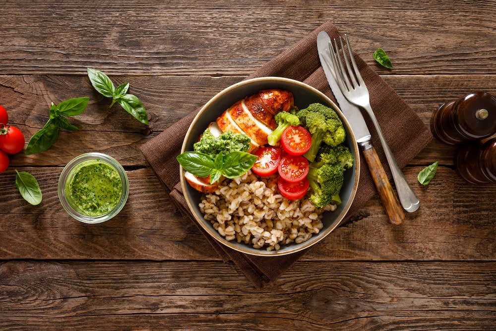 grain bowl with cooked chicken, tomatoes, broccoli, pesto, and a grain