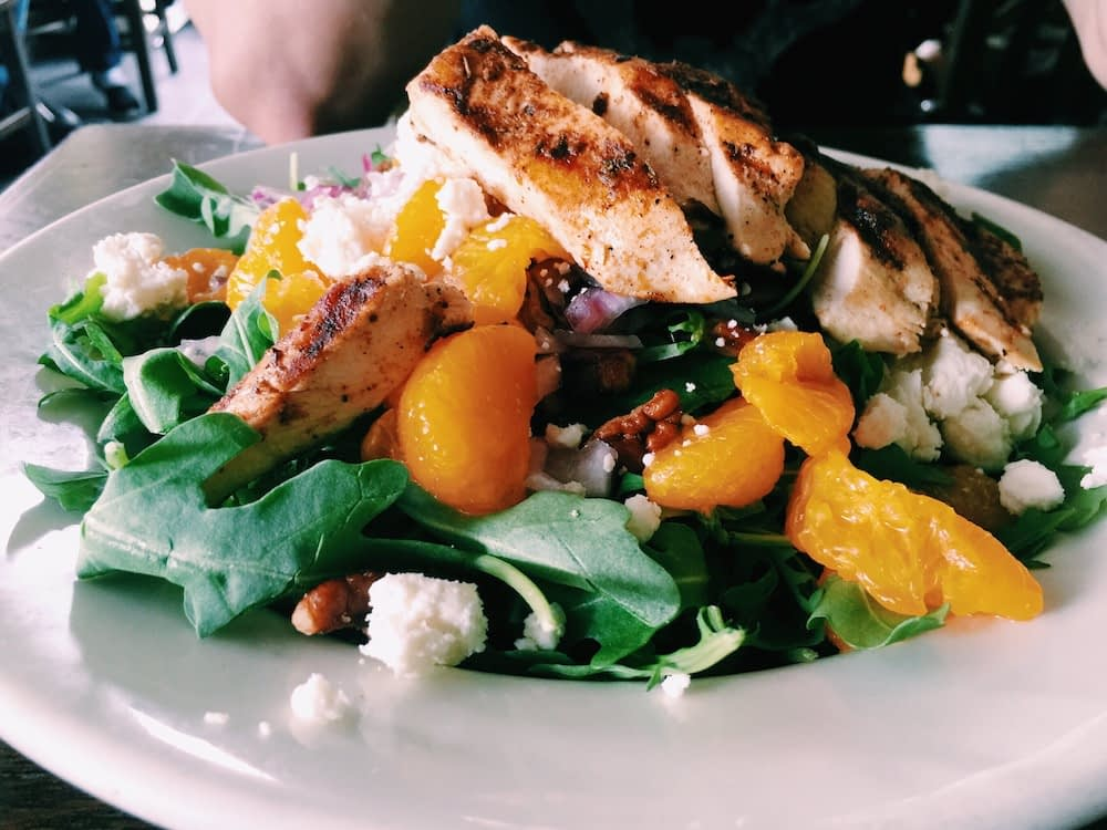 Salad with sliced grilled chicken, greens, tomatoes, and feta cheese